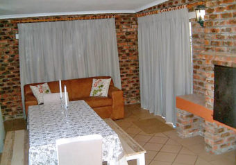 Spacious living room with an indoor braai/fireplace and dining table