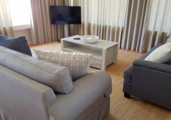 Open plan lounge with comfortable couches, a TV and DSTV